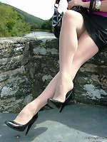 Fiery red head outdoors in pointy black high heeled shoes