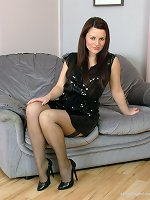 Gorgeous Sara is ready for a night out in a shiny black dress, silky stockings and matching high stilettos